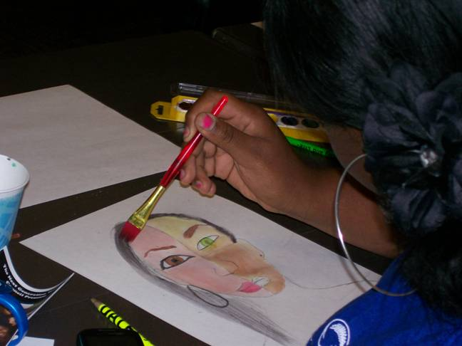 "Briana, 14, puts the finishing touches on her masterpiece during the ""Expressions through Art"" breakout session."
