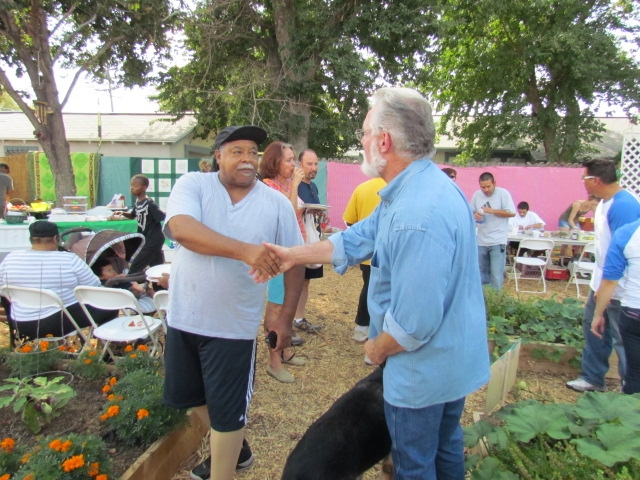 Wyatt Coleman of Lancaster shakes hands with Mayor R. Rex Parris at the Elm Avenue Community Garden