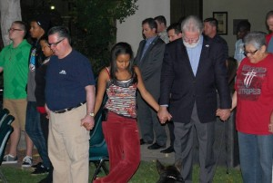 Mayor R. Rex Parris holds hands with residents as prayers are offered.