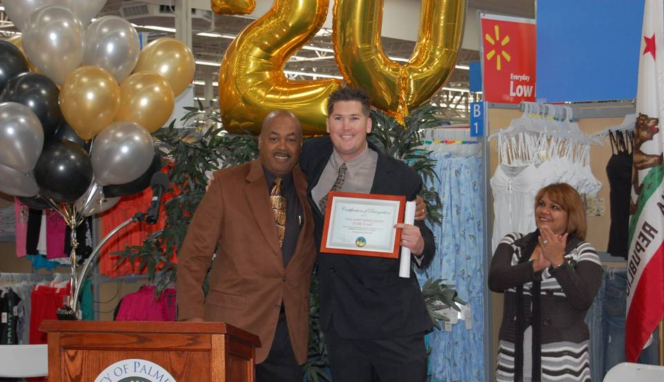 Walmart store manager Trent Blankenship(R) receives a certificate of appreciation from Antelope Valley Black Chamber of Commerce president Richard Poston(L) at a ceremony Wednesday celebrating Walmart's 20 years of business in Palmdale.