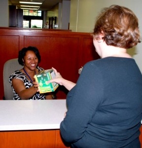 City employee Rochelle Scott presents a box of free compact florescent light bulbs.