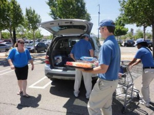 Helpful Guys in Blue carry groceries and load cars for shoppers around Sam's Club in Lancaster.