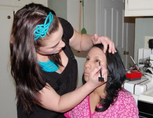 Tiffany Derosier applies make-up to caregiver Jennifer Nazario.