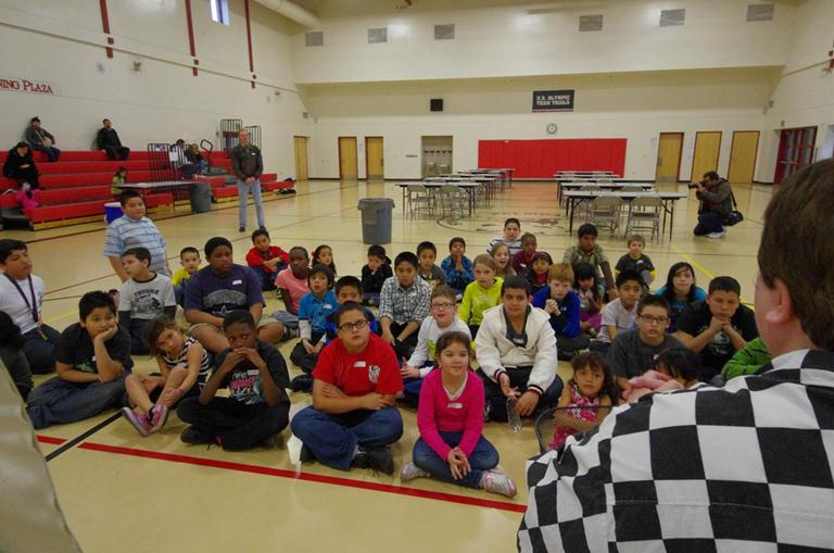 Tournament participants receive a chess lesson from Professional Chess Teacher Ms. Daa (right, in chess-squares shirt). In the background, the competition tables await.