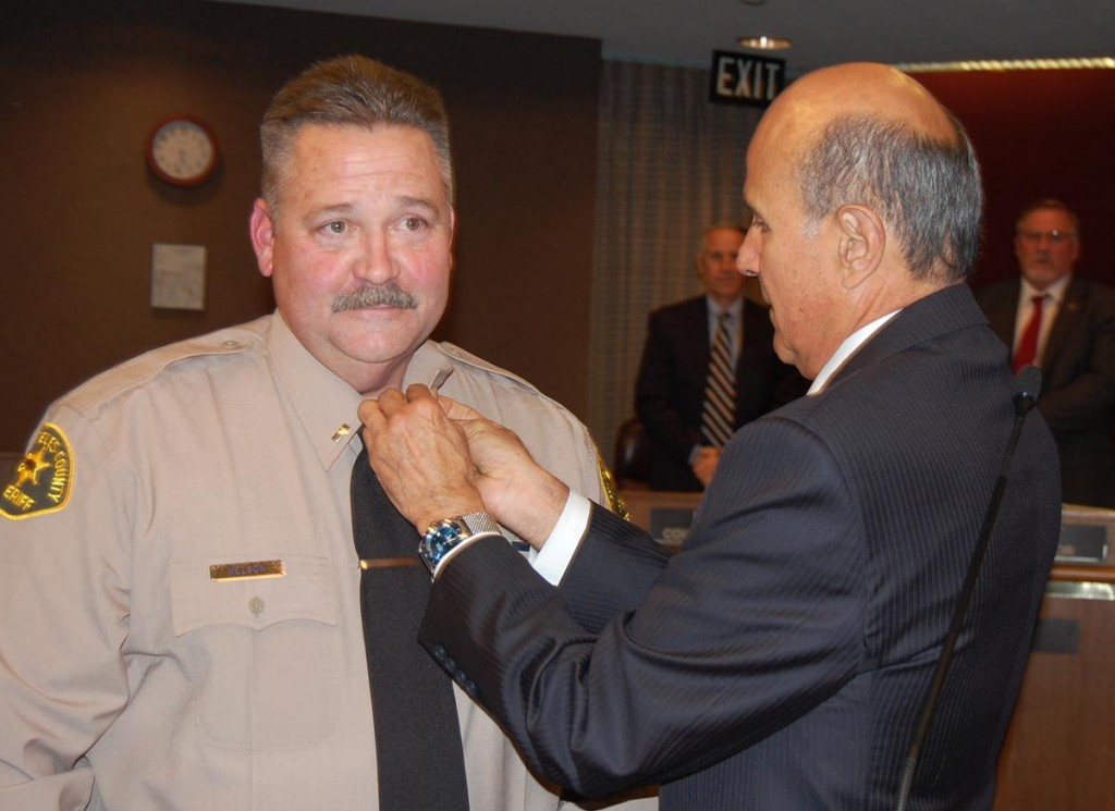 Los Angeles County Sheriff Lee Baca pins captain's bars on Pat Nelson, after promoting Nelson from Lieutenant to Captain at Tuesday's council meeting.