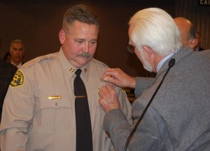 Mike Nelson pins on his son's badge. Baca said he and the elder Nelson shared a radio car in East Los Angeles in 1966.