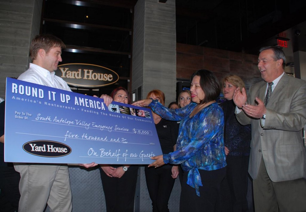 Yard House General Manager Mike Tomko (left) presents a check for $5,000 to Patricia Morales of SAVES, while Mayor Jim Ledford looks on.