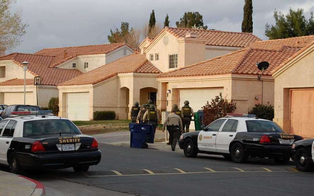 Deputies approach a home on Thursday morning 37600 block of Harvey Street in Palmdale. During the search deputies found several documents with gang writings, Gregg said. The juvenile who lives at the home was involved in a group assault on Jan. 17.
