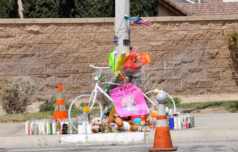 "A makeshift memorial, that includes dozens of candles, stuffed animals and flowers, marks the Palmdale intersection where Michael ""Speedy"" Valenzuela was struck by a school bus on March 25. A white bike showed up at the memorial on Saturday. It's the exact model that Valenzuela always wanted and had hoped to purchase, his friends said."