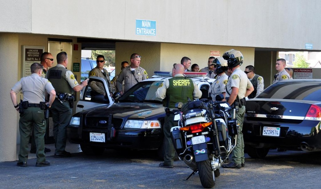 Deputies surround a patrol car in front of a medical office building where an attempted murder suspect was taken into custody Wednesday afternoon.