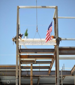 "Workers secure the final structural beam to the facility during the ""Topping Off"" celebration Friday (April 12)."