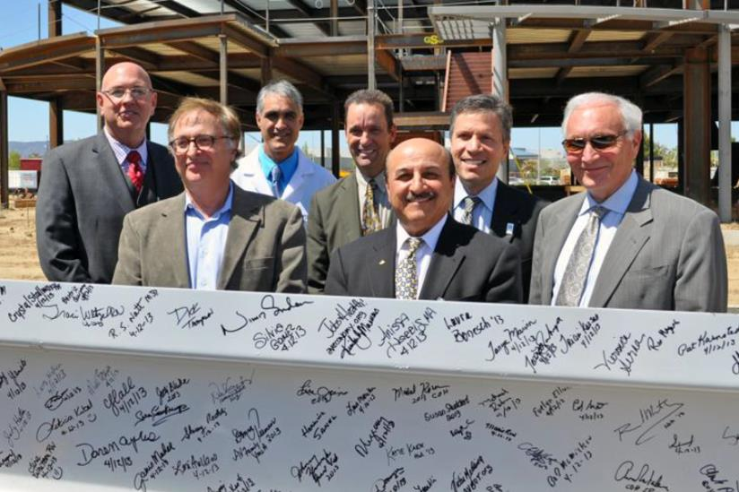 Executives from City of Hope, Antelope Valley Hospital, G.L. Bruno Associates, Inc., and local government officials pose with the beam prior to installation. (L to R) Norm Hickling, Abdallah Farrukh, M.D., Vijay Trisal, M.D., Senator Steve Knight, Edward Mirzabegian, Harlan Levine, M.D., Gary L. Bruno.