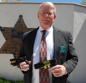 Captain Don Ford shows the size difference between the new and the old Tasers.